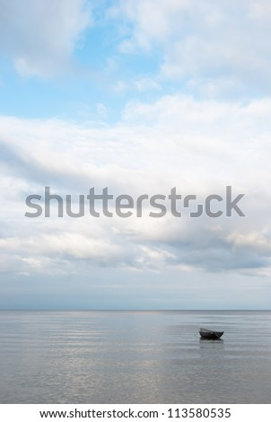 Lonely boat in a tranquil serene sea - stock photo