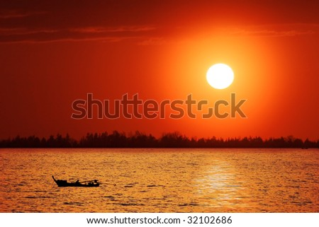 Lonely boat in the sea under sunset sky - stock photo