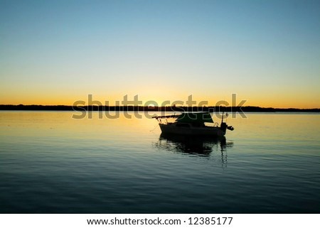 Lonely boat moored in a secluded bay just before dawn. - stock photo