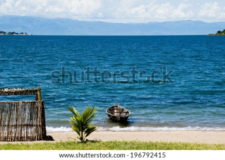 Lonely Boat on Lake Tanganyika / Lonely Boat next to a Shed on the Beach, Lake Tanganyika, Tanzania, Africa - stock photo