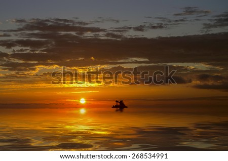 lonely boat on the horizon painted a vivid sunset - stock photo