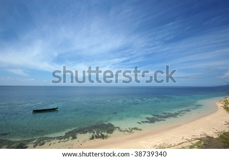 Lonely boat over transparent sea water. Indonesia. - stock photo