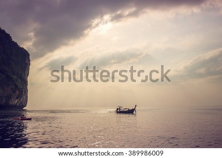 Lonely boat under beautiful sun rays at sunset in gorgeous Maya bay, Phi-Phi, Thailand. Image with selective focus and toning - stock photo