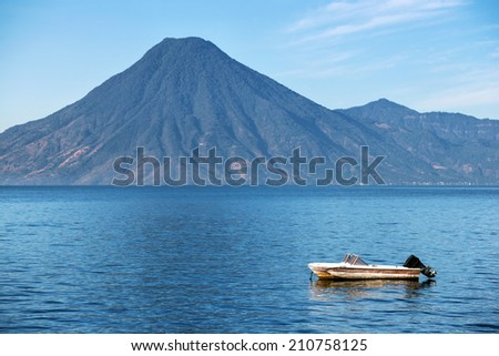 Lonely boat with volcano on the lake Atitlan in Guatemala - stock photo