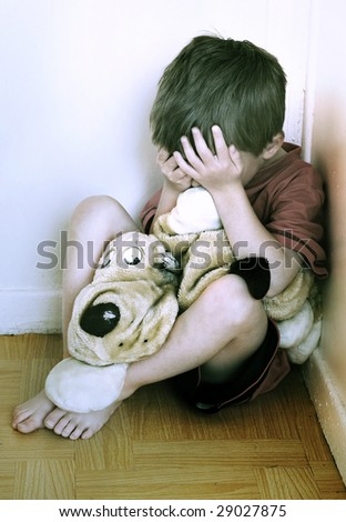 Lonely boy being punished in the corner. (This image is toned intentionally) - stock photo