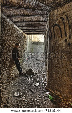 lonely boy in grungy tunnel, deep in thought - stock photo