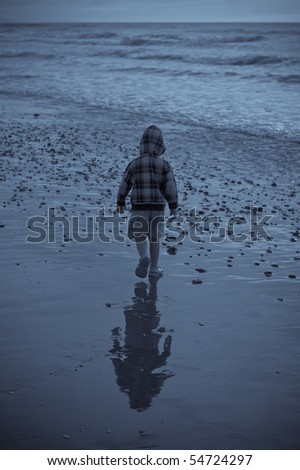Lonely boy walking  on the beach looking for stones in the sand. - stock photo