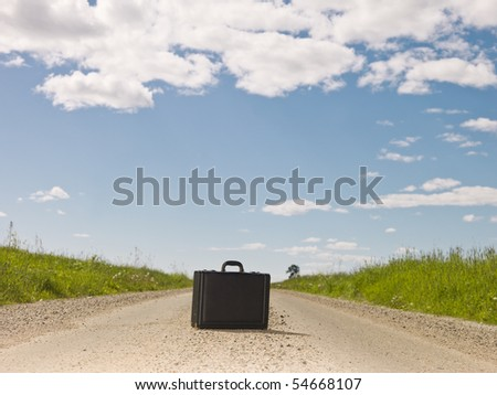 Lonely briefcase on a Dirt Road - stock photo