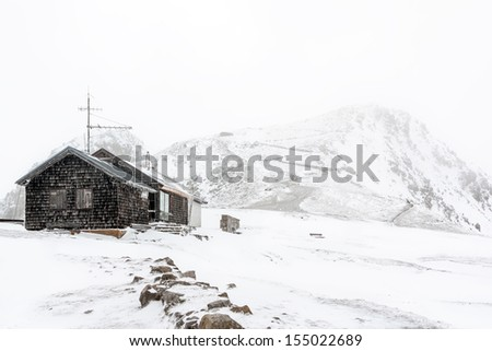 Lonely building on the top of a snowy hill.