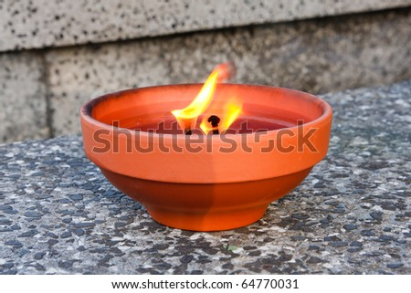 Lonely burning candle standing on a gravestone - stock photo