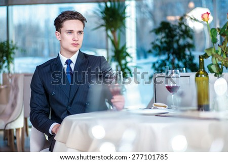 Lonely businessman. Confident businessman in formal wear sitting at a table in a restaurant while holding a glass of wine and looking ahead - stock photo