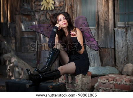 Lonely Caucasian fairy sits on bricks and smokes a cigar - stock photo
