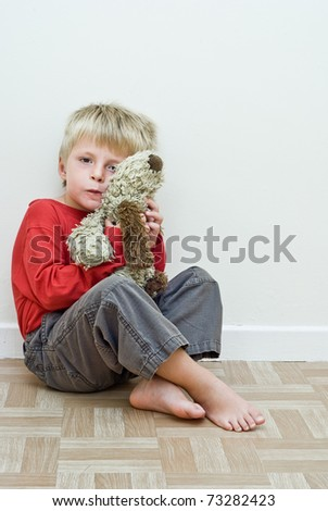Lonely child sits on the floor holding his soft toy - stock photo