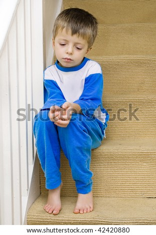 Lonely child sits on the stairs. - stock photo