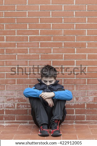 lonely child sitting by himself  - stock photo