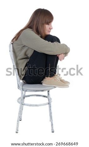 Lonely, closed woman sitting on chair. Isolated over white background. - stock photo