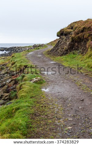 Lonely coastal dirt track near Dunvegan castle in Skye in the highlands of Scotland. The windy path passes beside the loch and the cliff while diminishing towards the vanishing point in the horizon. - stock photo
