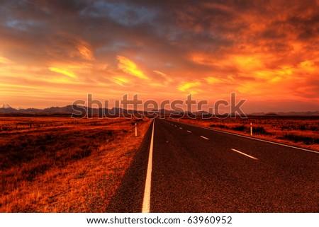 lonely country road landscape in vibrant colors - stock photo
