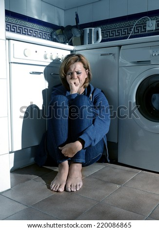 lonely depressed and sick woman sitting alone crying on kitchen floor in stress suffering depression and sadness feeling miserable in barefoot looking desperate - stock photo
