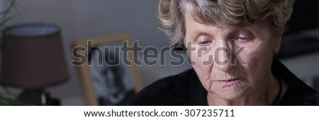 Lonely depressed widow missing for dead husband - stock photo