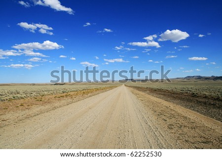 lonely dirt road runs across the Wyoming plains to a distant horizon with blue sky and clouds - stock photo