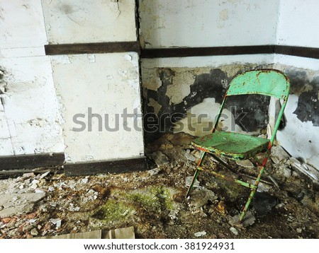 Lonely dirty green chair inside abandoned grungy room - landscape color photo - stock photo