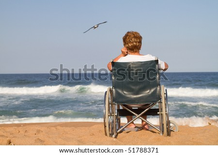 lonely disabled senior woman on beach - stock photo