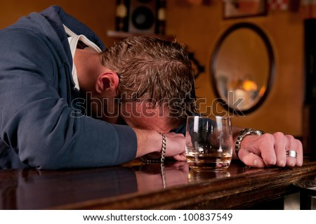 Lonely drunk man who has had one too many glasses of alcohol at the bar and has passed out on the countertop - stock photo