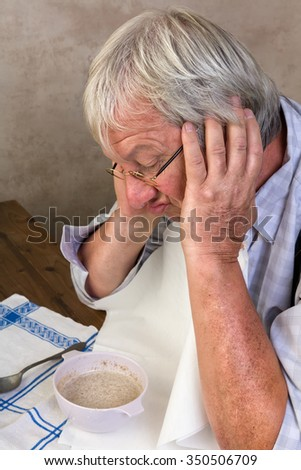 Lonely elderly man disliking his porridge breakfast in the morning - stock photo