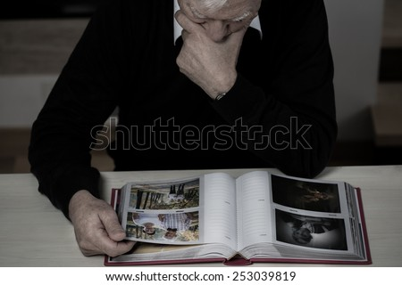 Lonely elderly man recollect happy memories from his life - stock photo