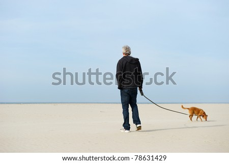 Lonely elderly man with dog at the beach - stock photo