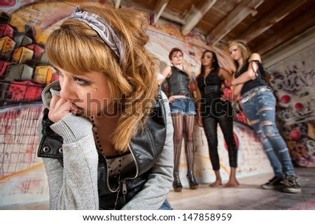 Lonely female being teased by group of people - stock photo