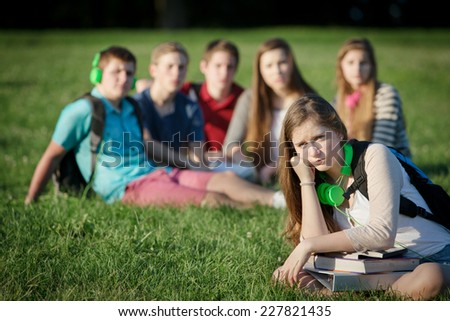 Lonely female teen student sitting near group