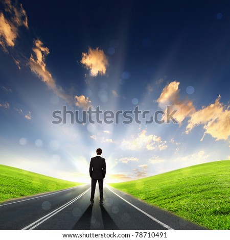 lonely figure, empty road leading toward horizon and cloudy sky - stock photo