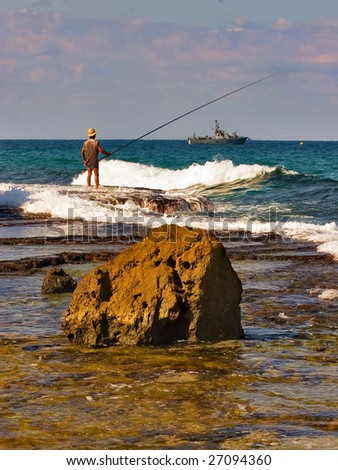 Lonely fisherman on a sunny sea shore - stock photo