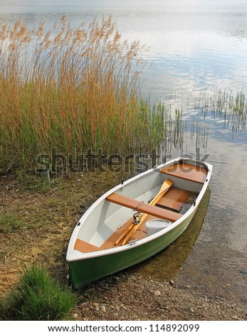 lonely fishing boat on the lakeside - stock photo