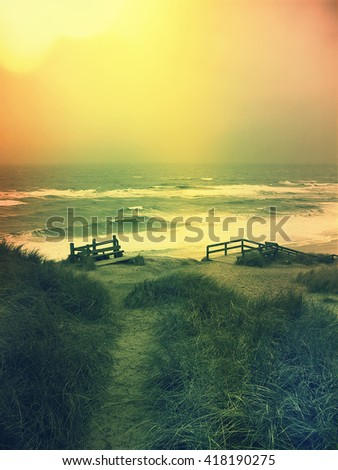 Lonely footpath and stairway through a beach dune. Beach on Sylt. - stock photo
