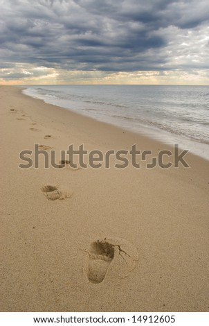 Lonely footprints on a sandy beach, under dark stormy clouds at sunset - stock photo