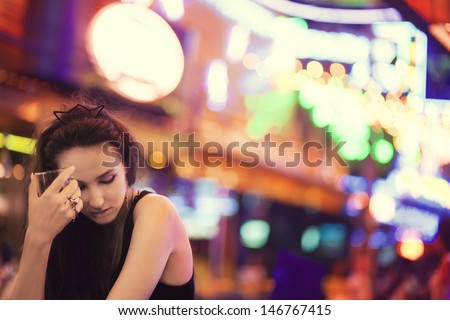 Lonely girl is drinking in a bar one night - stock photo