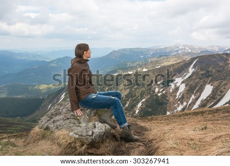 Lonely girl is sitting on a mountain top - stock photo