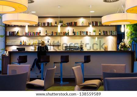 lonely girl sits alone at modern illuminated hotel bar - stock photo