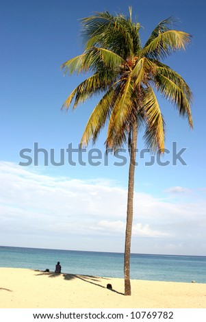 Lonely girl sitting on sand near the ocean - stock photo