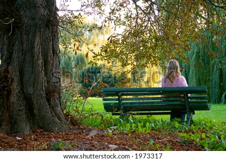 Lonely girl sitting on the bench near the oak