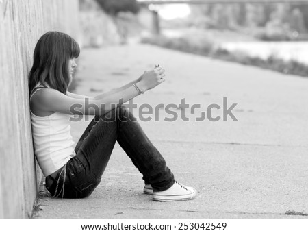 Lonely girl sitting on the concrete ground in urban environment. - stock photo