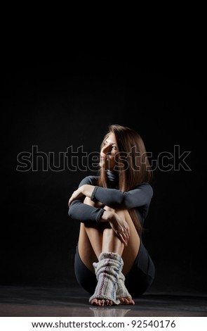 lonely girl sitting on the floor propped his feet under him - stock photo