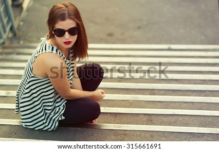 Lonely girl sitting on the stairs. Toned image - stock photo