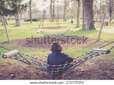 lonely girl thinking in a hammock - stock photo