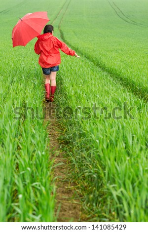 Lonely girl walking in the rain in rubber boots - stock photo