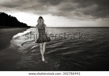 lonely girl walking on a beach with sea and stormy sky - stock photo