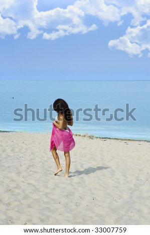 lonely girl walking on the beach near the sea with a red pareo